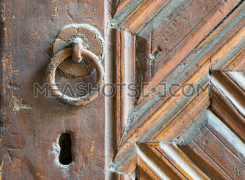 Closeup of rusted ring door knob over an aged decorated wooden door, Old Cairo, Egypt