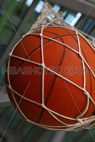Close up one basketball ball hanging in mesh sack, low angle side view