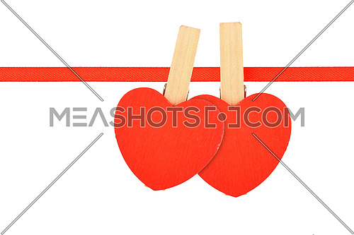 Valentine day love template, two red wooden hearts with clothes pins on textile ribbon isolated on white background
