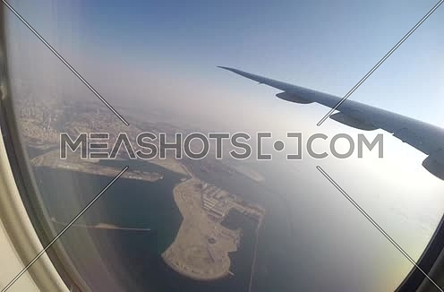 shot from plane window showing wing flying over Dubai city at day