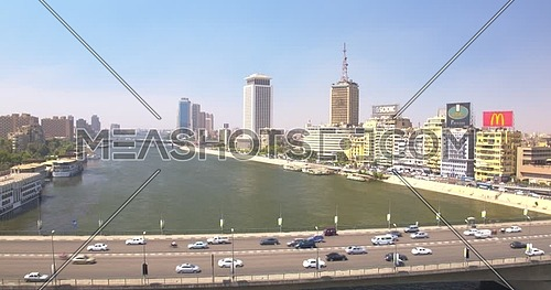 Fly over shot of The River Nile revealing Bridge, traffic, Hilton Ramsis Hotel at day