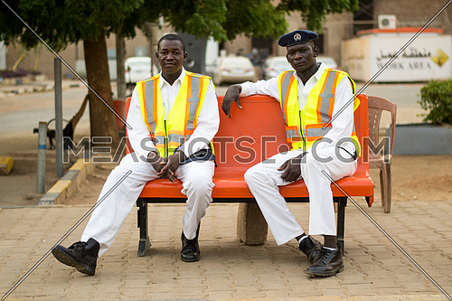 two sudanese traffic police men sitting on a bench posing to the camera