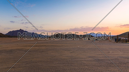 Wonderful landscape,Arabian desert of stone, Egypt with mountains at sunset.To the right of the desert nomad huts,