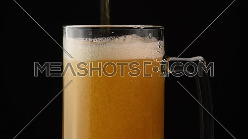 Close up background of pouring lager beer with bubbles and froth in glass mug over black background, overfill and run out, flowing over the top
