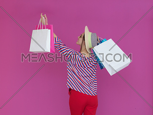 Young woman with shopping bags on pink background. Happy girl posing with new purchases after a day of big sale. Black Friday concept