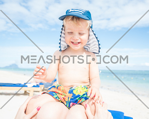 Smiling baby boy sitting at mom in her legs on the beach.