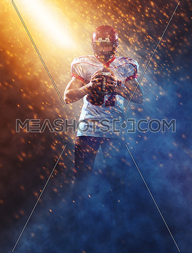 portrait of confident American football player holding ball while standing on the big field with particles effects and lights