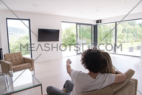 Rear view of couple watching television in living room their luxury home