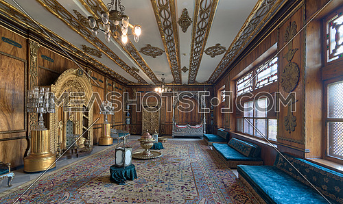 Cairo, Egypt - October 21, 2017: Manial Palace of Prince Mohammed Ali Tawfik. Residence of prince's mother with golden ornate niche, silver bed, golden wardrobe, blue couches, ornate wooden wall and ceiling