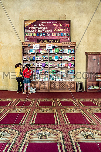 two girls  standing looking towards the Discover Islam free book section for tourists