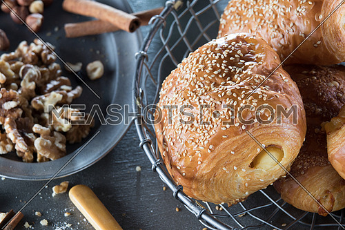 Freshly baked pastry in a metal basket surrounded by nuts and dry food