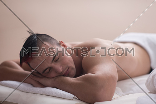 attractive handsome man resting in a spa massage center, lying on table relaxing closed eyes  concept of men beauty health care