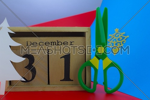 Paper cut figure of christmas tree with green toy scissors next to a wooden calendar showing December 31st. Close-up composition for New Years concept on blue and red background
