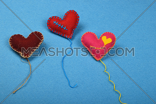 Felt craft and art, three handmade stitched toy hearts with threads, red, pink and brown on blue background