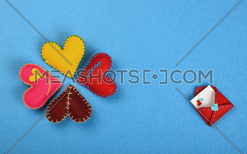 Felt craft and art, four colorful  handmade stitched toy hearts, red, pink, yellow, brown and envelope on blue background