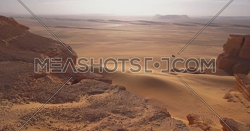 Aerial shot for 4x4 Car moving through sand dunes in the desert at sunrise