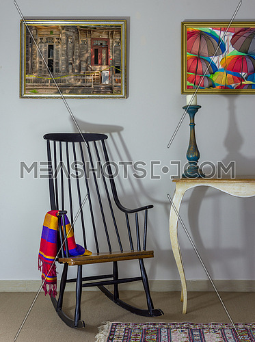 Interior shot of vintage rocking chair, old style table, candlestick on background of off white wall with two hanged paintings including clipping path for paintings