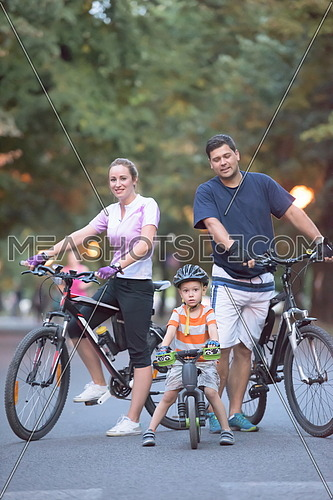 portrait of happy young family with bicycles in park at night