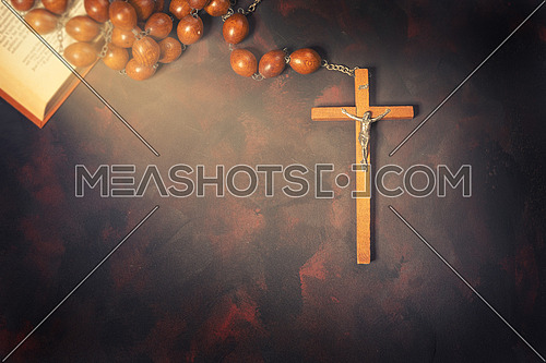 Big wooden Rosary beads and crucifix cross with jesus,red candle and bible book,spiritual atmosphere ,religion concept.
