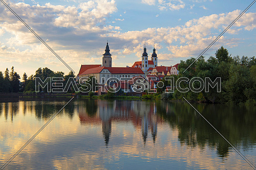 Our Lady Monastery (The Abbey of Nova Rise) with reflection over calm waters of lake and cloudy sunset sky in Telc, Moravia, Czech Republic