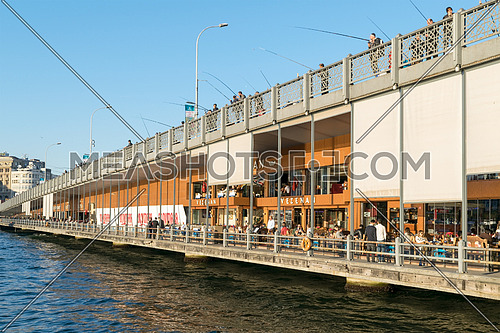 Istanbul, Turkey - April 25, 2017: Galata Bridge with traditional fish restaurants and fishermen fishing