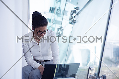 busy businesswoman have conference call and online presentation while working on laptop computer and sitting by big window of modern corporate business office