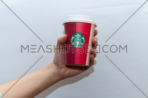 A female holding a Starbucks takeaway paper cup, in special design for Christmas on a white background; December 2018 - Cairo, Egypt.