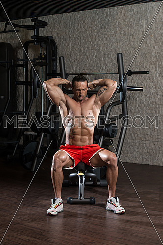 Muscular Mature Man Doing Heavy Weight Exercise For Triceps In Modern Fitness Center