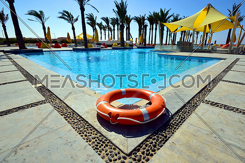 A low angle perspective of a swimming pool showing orange emergency floater in the corner