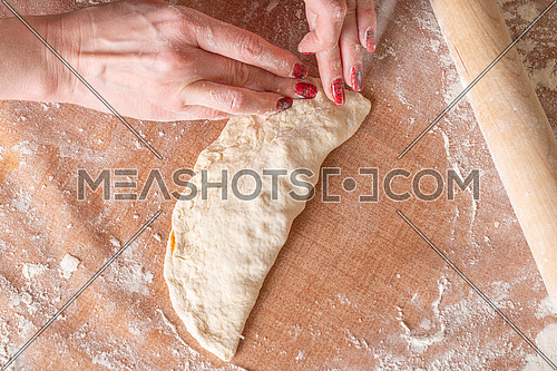 Making dough by female hands brown table background,view from above.