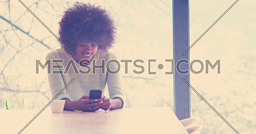 Handsome young african american woman drinking coffee and using a mobile phone at  home