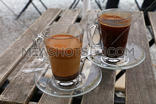 Two full Turkish freshly brewed natural ground coffee, black and with milk, in transparent full glass cups with saucer and metal spoons over vintage wooden table, close up, high angle view
