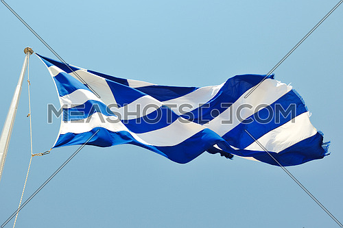 greece flag in wind at day with blue background