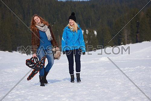 female friends in beautiful winter day have relaxed walk on snow and. holding snowshoes