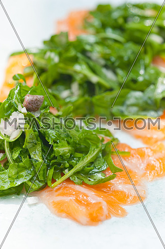 fresh salmon carpaccio sushi sashimi with arugula rocket salad and caper on top