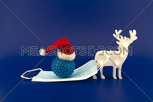 Christmas deer scene with coronavirus gift on the sleigh made of medical face mask. Concept of holidays during covid pandemic isolated on blue background