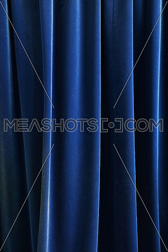 Heavy dark navy blue pleated textile curtain background with portiere drape folds, side view close up
