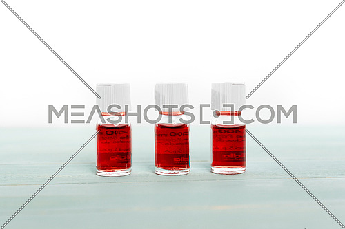 Three medicine vials filled with red liquid arranged in a row on white background