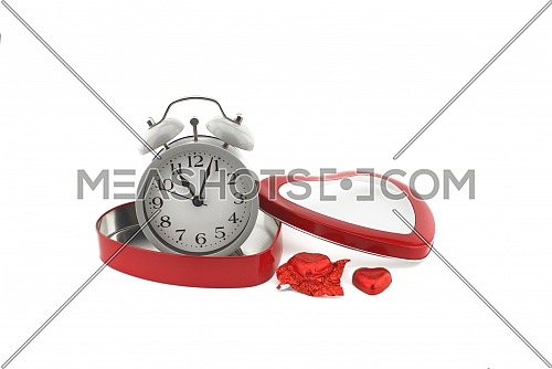 Retro alarm clock in a red heart shaped box with chocolate candy alongside on a white background with copyspace symbolic of love, togetherness and romance for Valentines