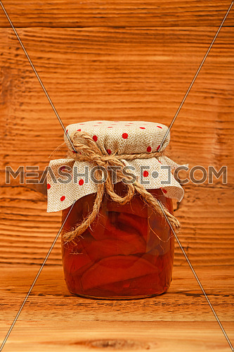 One glass jar of homemade quince jam with textile top decoration at unpainted brown vintage wood