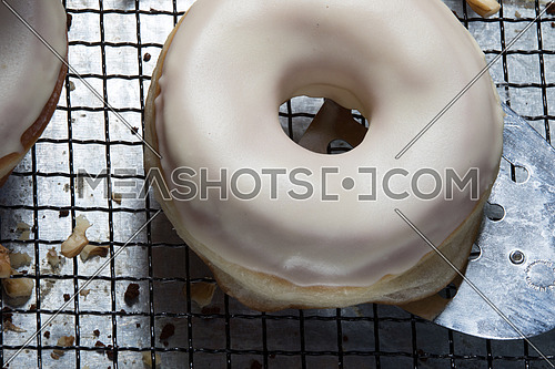 top view of white glazed donuts and walnuts