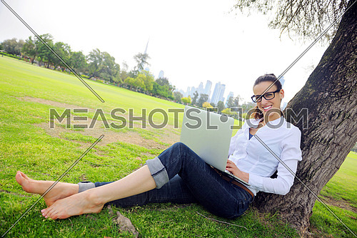 happy young student woman with laptop in city park study