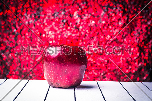 Red apple on a white wooden table over bokeh background