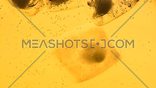 Extreme close up sparkling wine, soda water or lemonade with ice in glass, one ice cube falls in dropped, low angle side view, slow motion