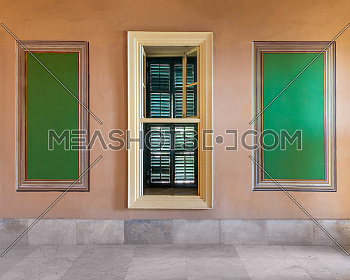 Narrow wooden window with closed green shutters mediating two beautiful elegant rectangular green frames on orange wall with white marble floor, in abandoned old building