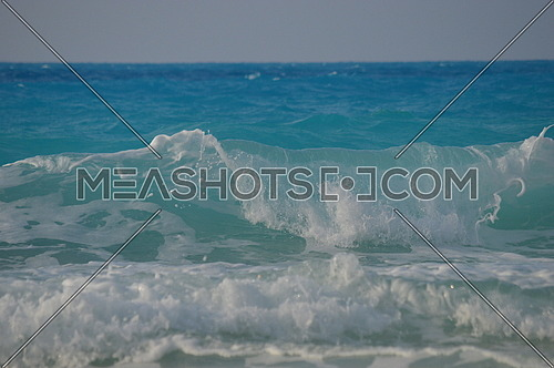 Clear Blue Sea waves hitting the shore