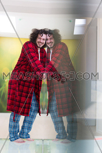 portrait of young man in bathrobe enjoying free time at home