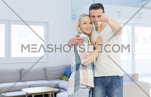 Happy smiling young couple hugging while showing a keys of their new house