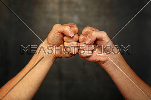 Close up two woman arms bumping fist to fist in boxing greeting gesture, against each other over dark background, low angle side view