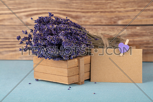 Close up bouquet of dried lavender flowers and small brown paper note on blue tablecloth, high angle view